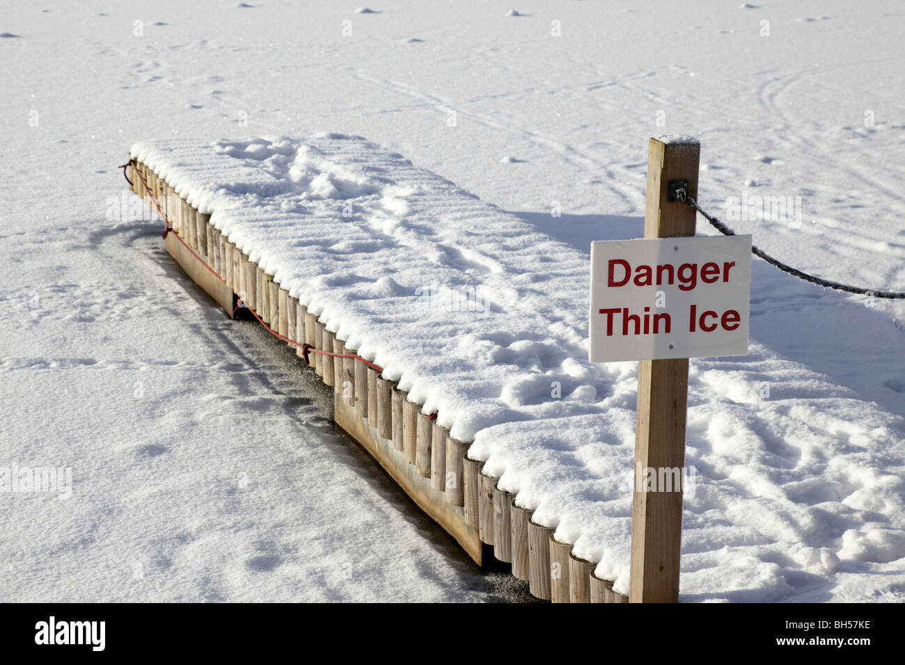 danger thin ice sign on a wooden jetty leading to a frozen lake centre parcs penrith uk - Stock Image