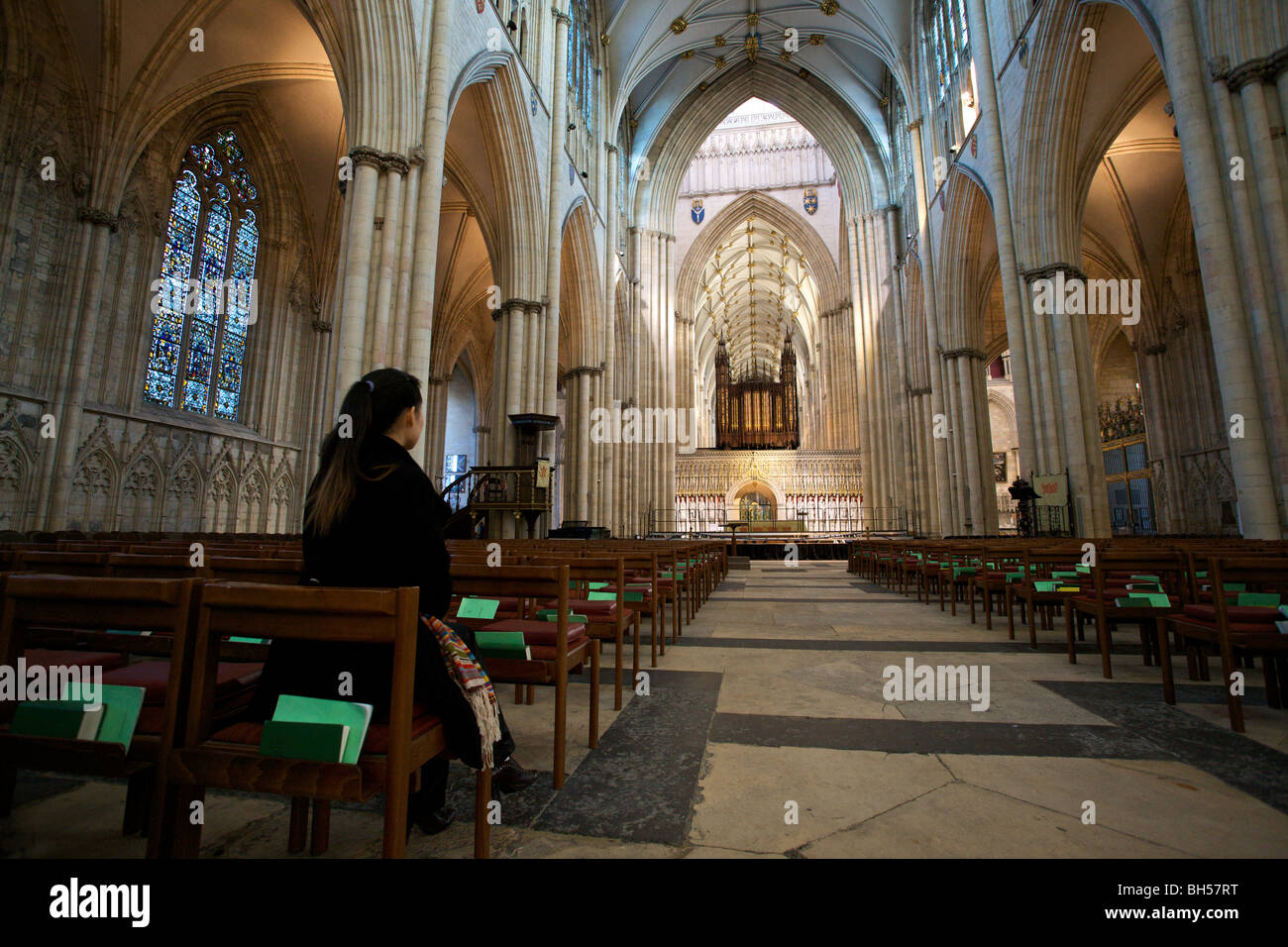 A girl sits alone on the pews in York Minster Abbey, UK Stock Photo