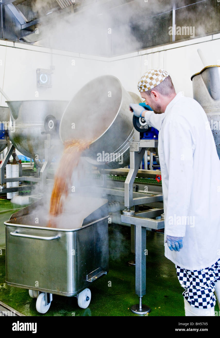 Inside a food factory making jams, pickles and condiments showing a male worker emptying a cauldron of pickles into - Stock Image
