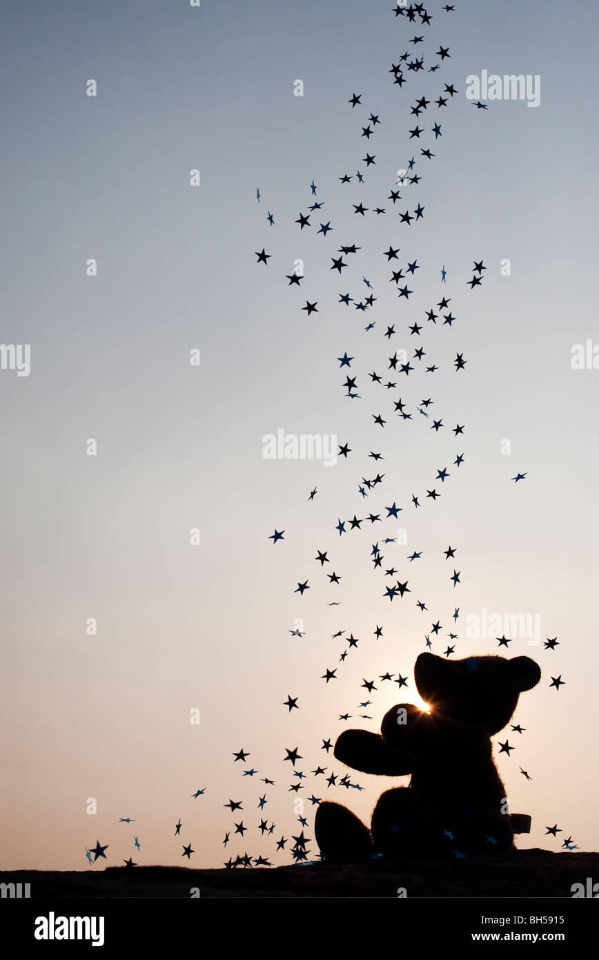 Teddy bear catching falling stars silhouette - Stock Image