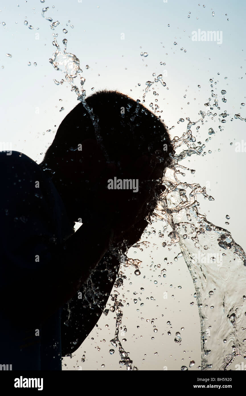 Indian boy splashing water on himself silhouette. Andhra Pradesh. India - Stock Image