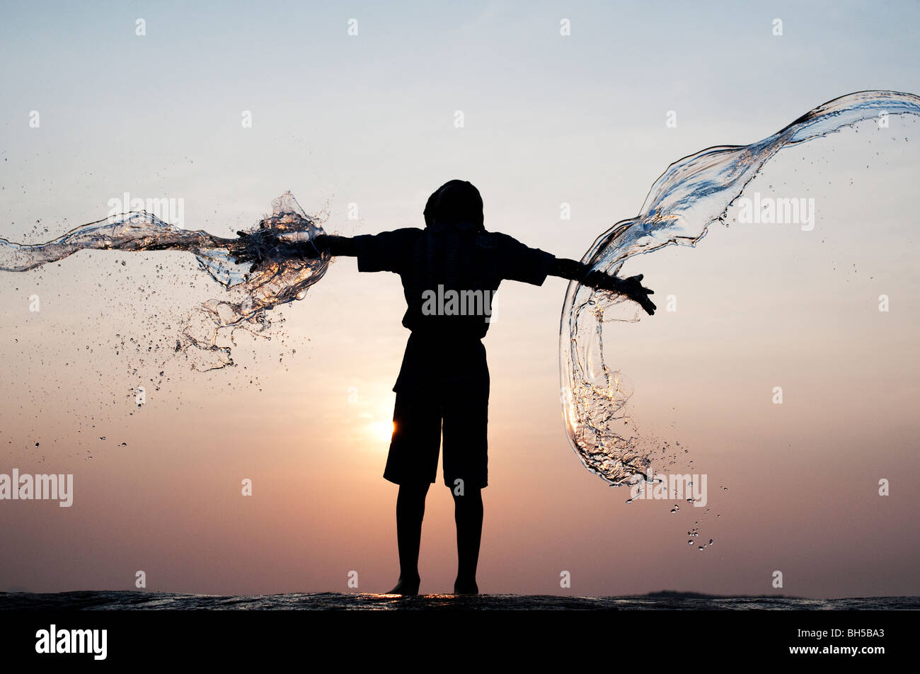 Indian boy having water thrown at him against an indian sunset. Silhouette. Andhra Pradesh, India - Stock Image