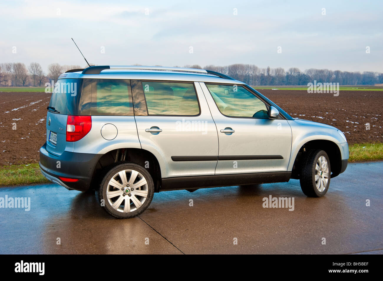 Rear, side view Skoda Yeti crossover SUV, 2010 model in light blue metallic parked on a street next to a field - Stock Image