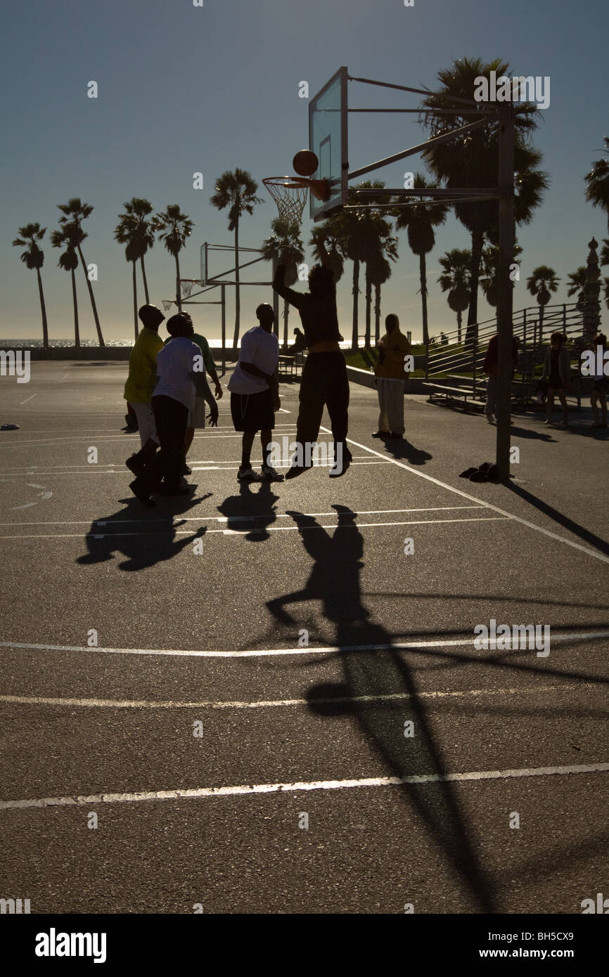 Men playing basketball on a sunny day at Venice Beach, Los Angeles, California, US - Stock Image