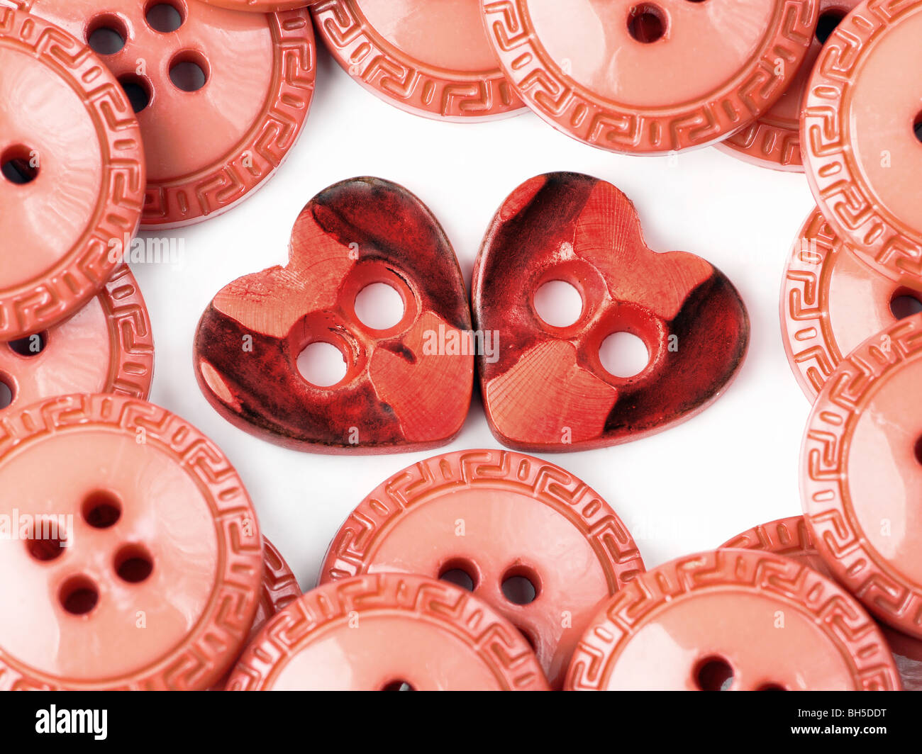 Two heart-shaped buttons surrounded by round buttons - Stock Image