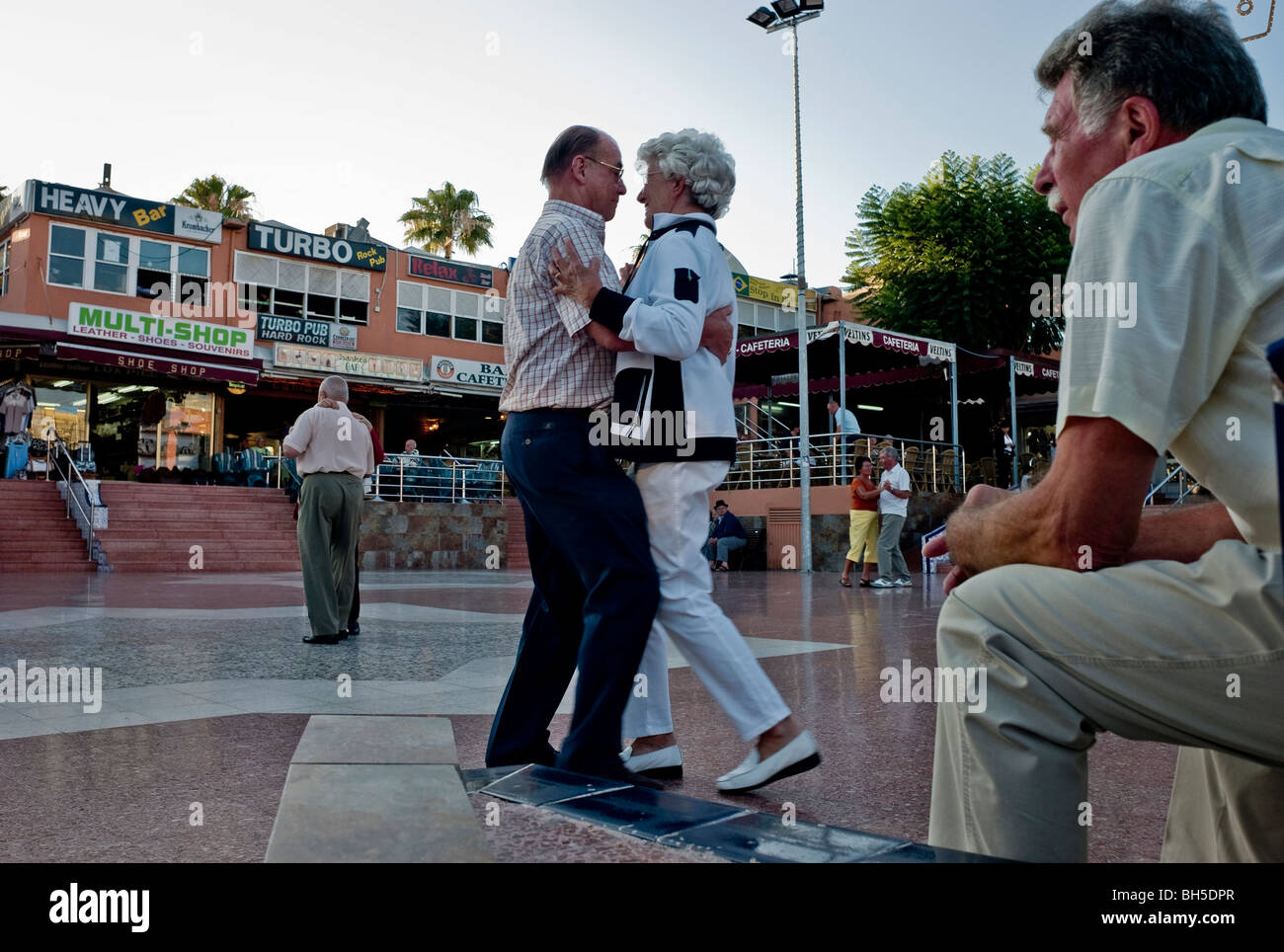 A an elderly couple dancing in the open air market part of the Kasbah Centre in Playa del Ingels Gran Canaria Spain - Stock Image