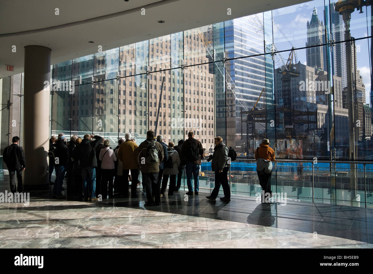 A group of tourists look out of the windows of the World Financial Center onto the site of Ground Zero in Manhattan, - Stock Image
