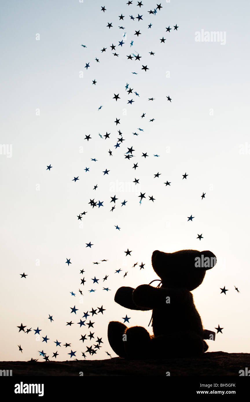 Teddy bear catching falling stars silhouette Stock Photo