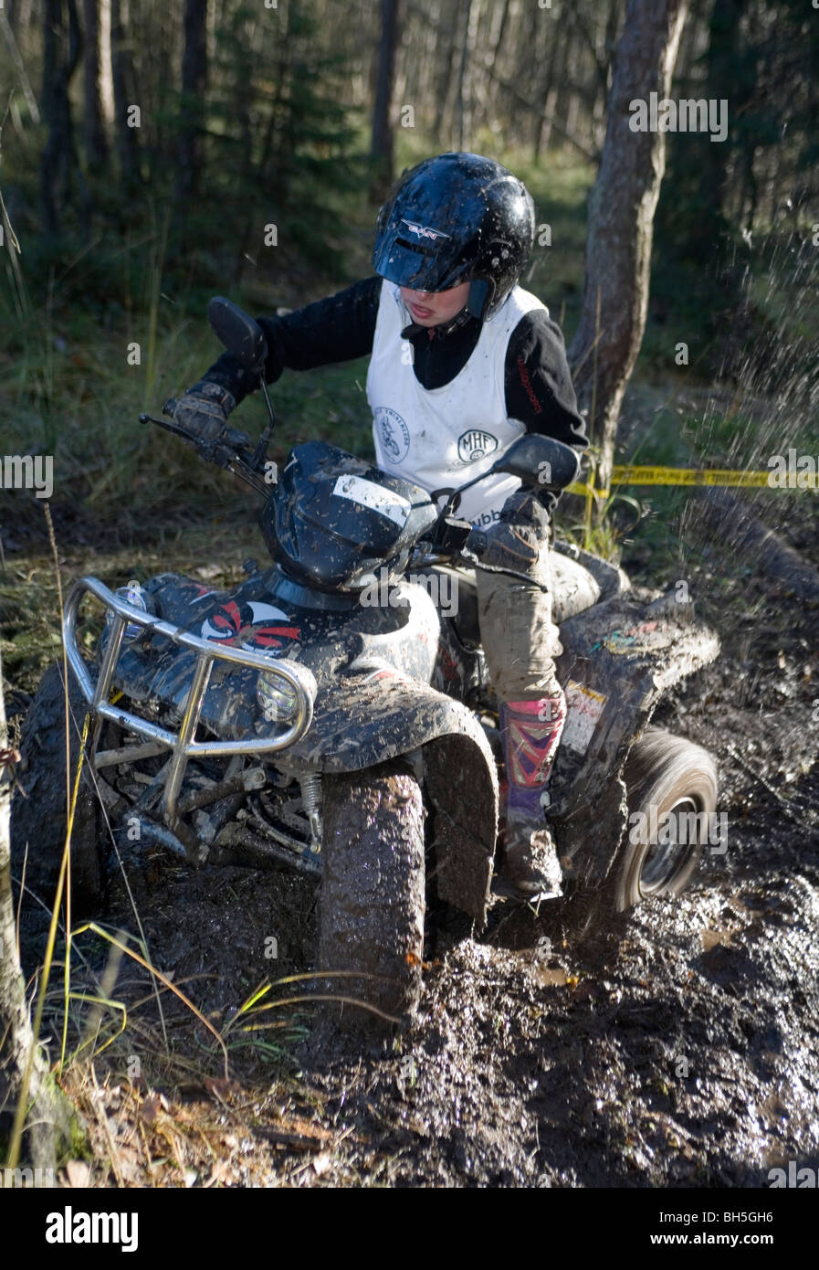 4 wheel trial. A boy rides all terrain vehicle off road - Stock Image