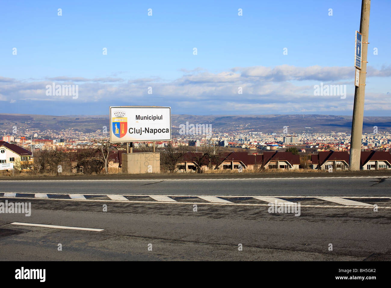 Cluj-Napoca city limits sign with the city in the background. - Stock Image