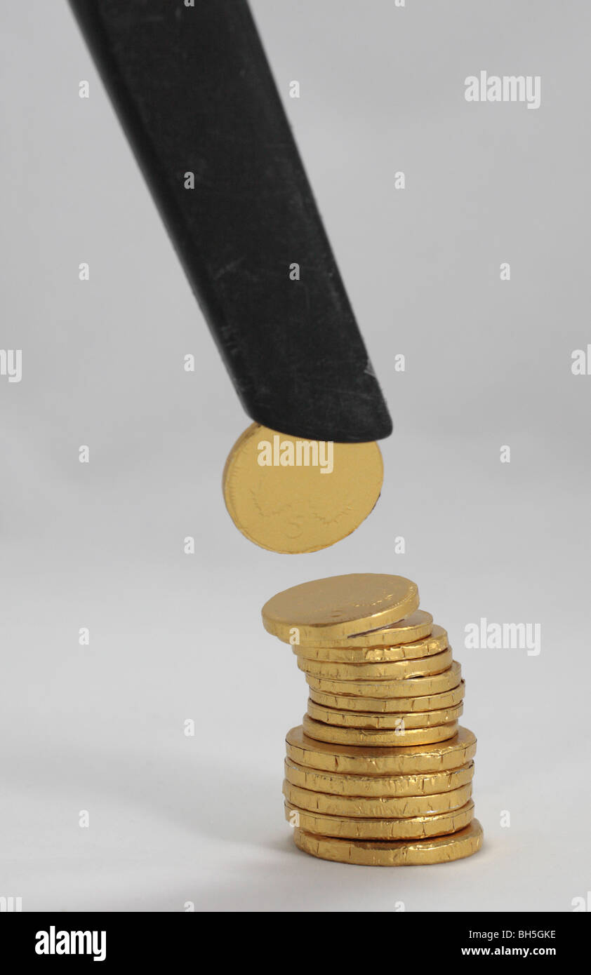 A stack of chocolate coins with one being 'sucked' off the top symbolising depreciation, recession, disappearing - Stock Image