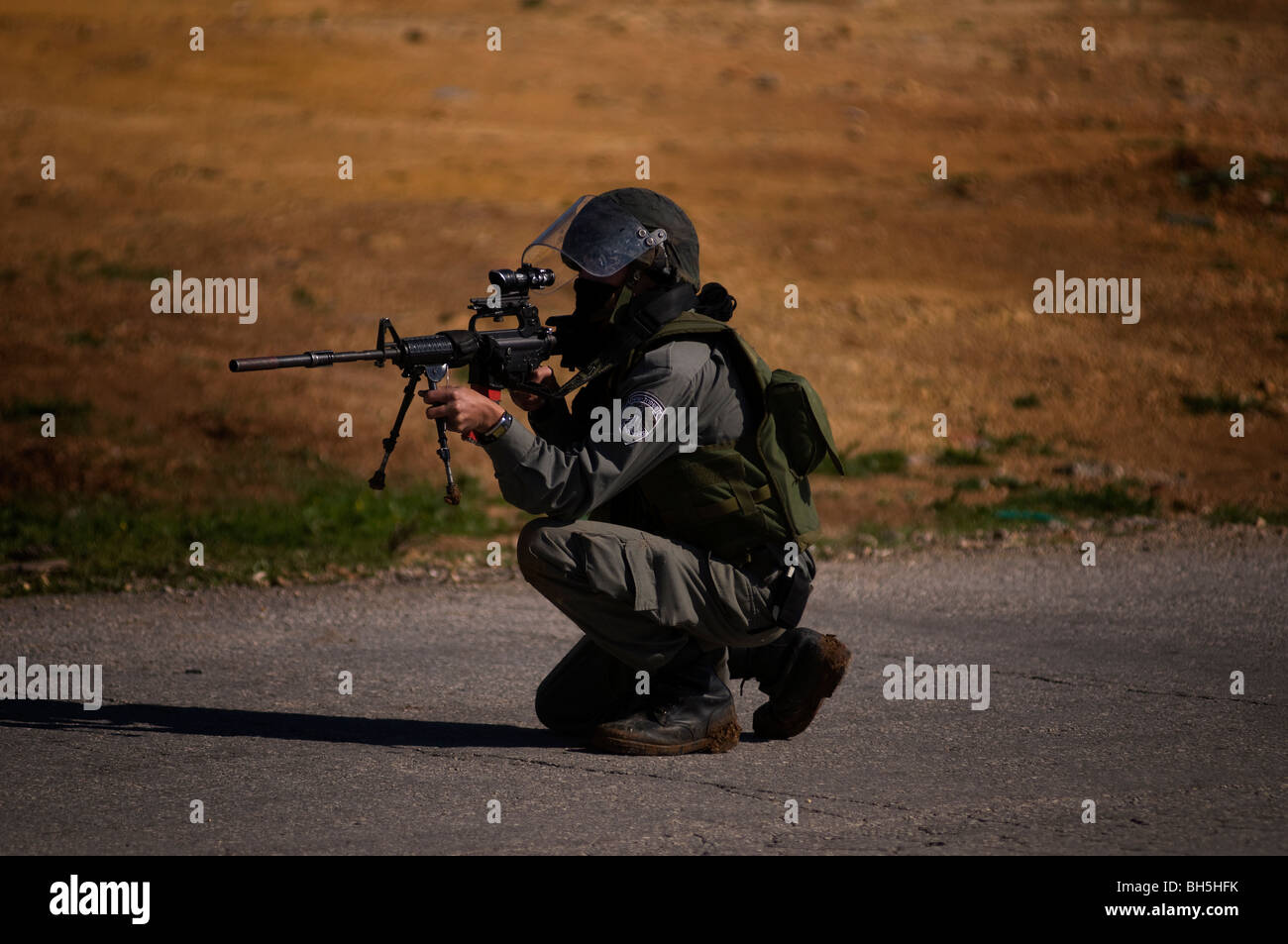 An Israeli border policeman fires rubber bullets towards Palestinian demonstrators during a protest in the West - Stock Image