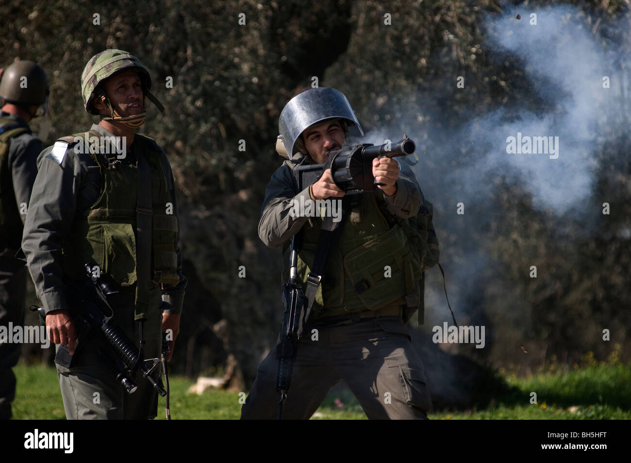 An Israeli border policeman fires tear gas canister towards Palestinian demonstrators during a protest in the West - Stock Image