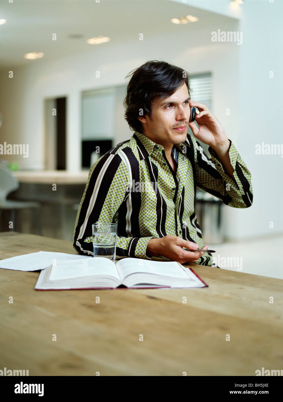 Businessman talks on mobile phone - Stock Image