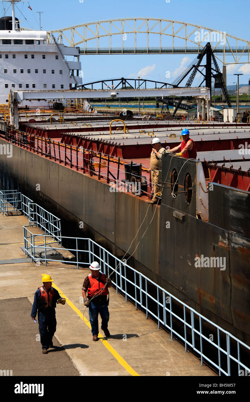 Dock side workers taking the lines of a lake freighter passing through MacArthur Lock. Sault Ste. Marie, Michigan, - Stock Image