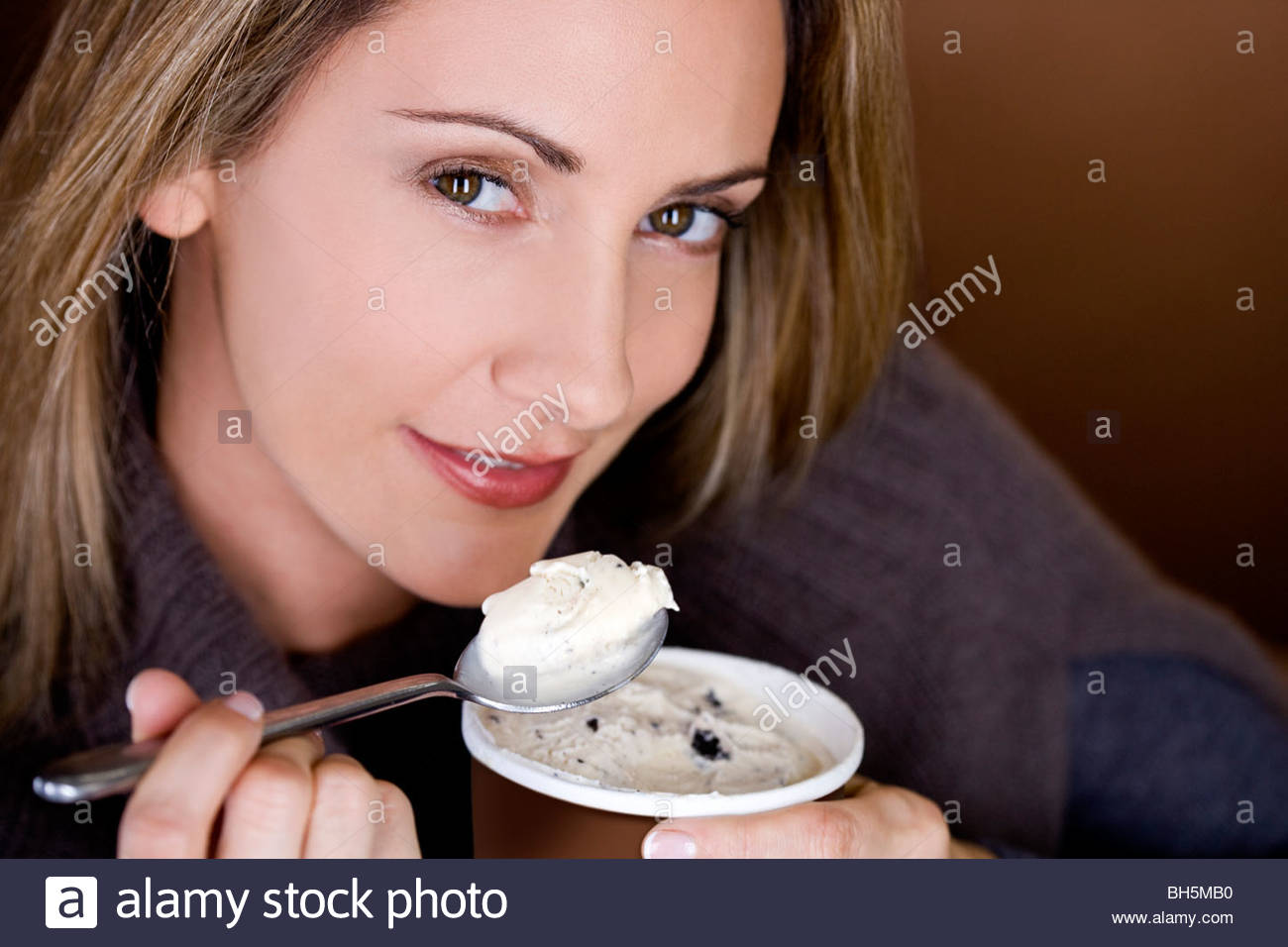 A mid adult woman eating ice cream, close-up - Stock Image