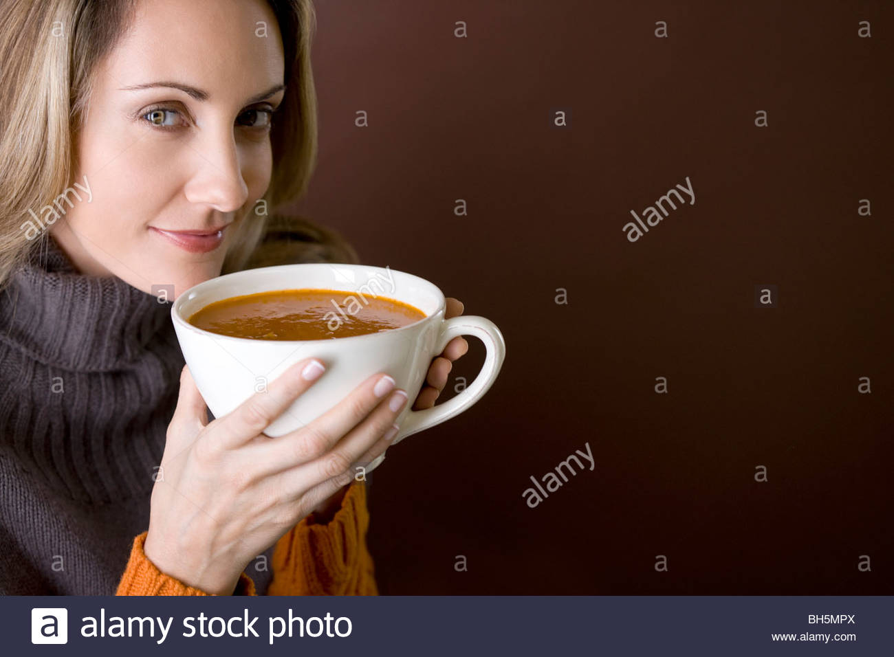 A mid adult woman holding a cup of soup - Stock Image