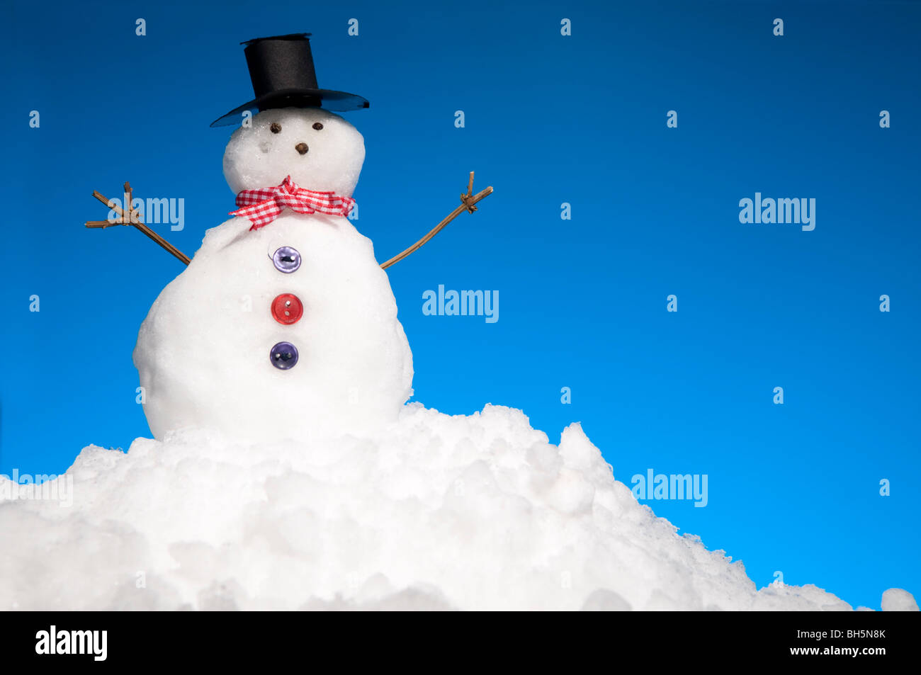 Miniature Snowman On Mound Of Snow With Blue Sky Behind - Stock Image