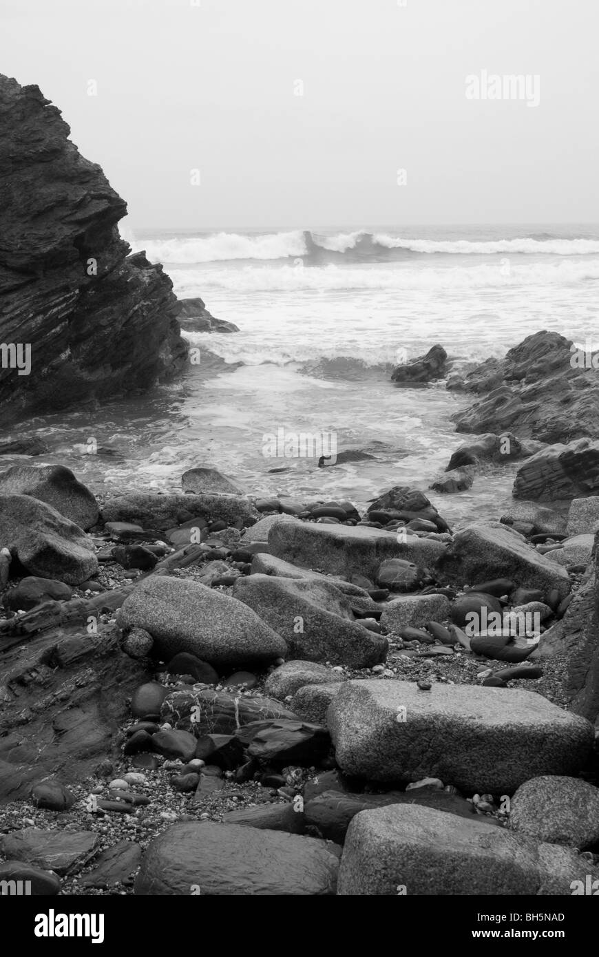 Rocky foreshore with surf breaking on a Cornish beach in black and white - Stock Image