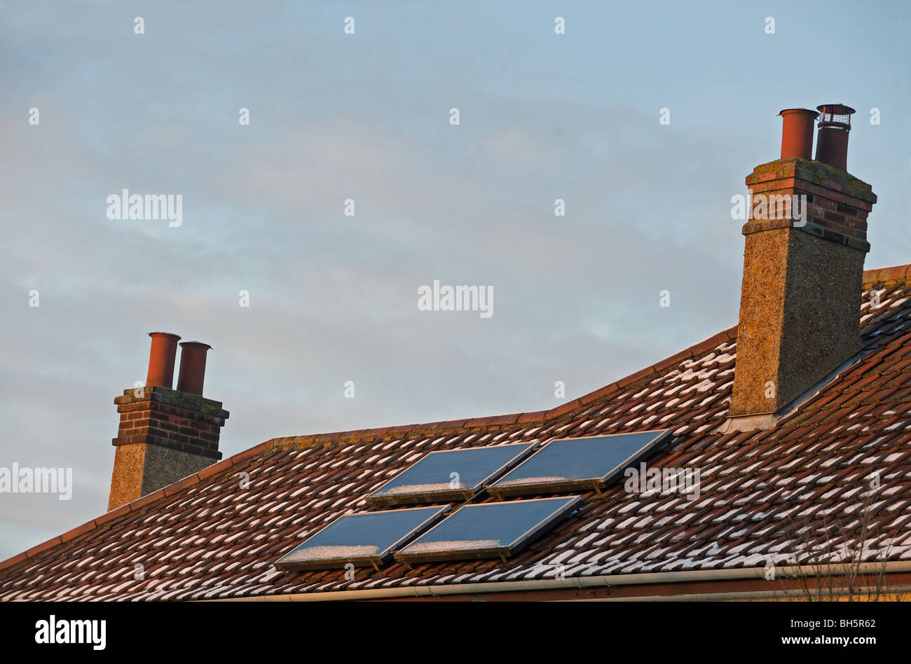 Solar panels fitted to the roof of a house in the UK. - Stock Image