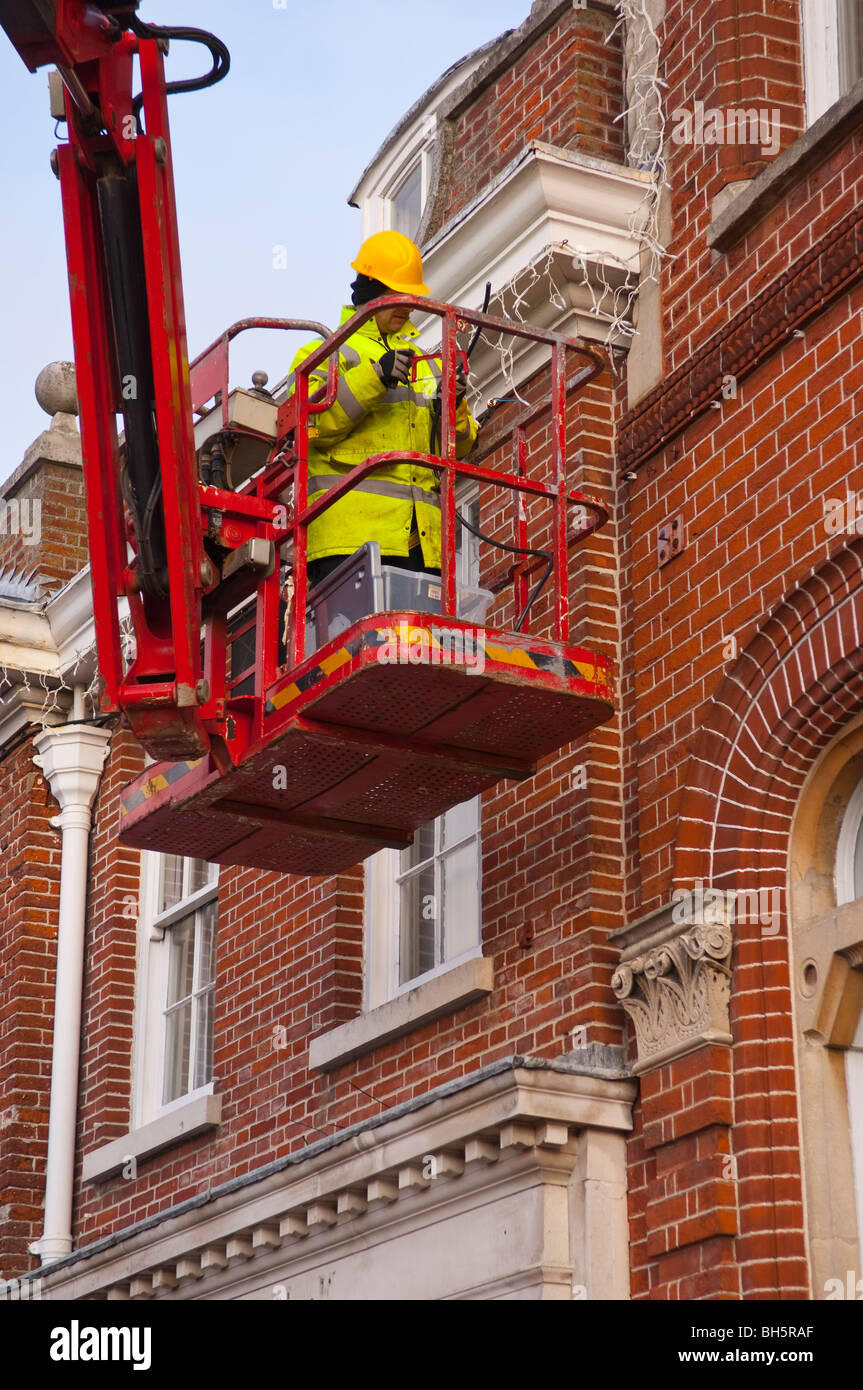 A Workman Putting Up Christmas Lights On A Cherry Picker In