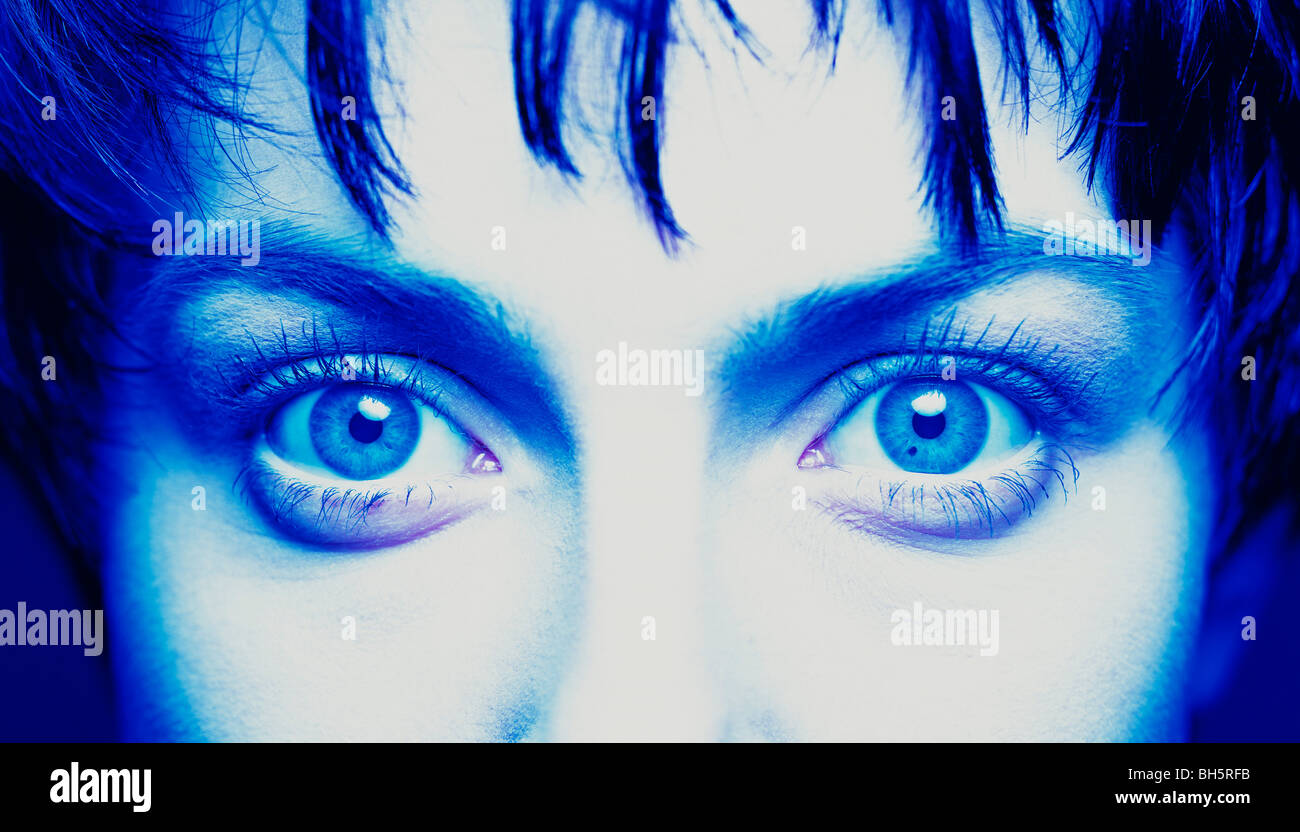 Woman starring with blue eyes, close-up with a monochromatic blue tone - Stock Image