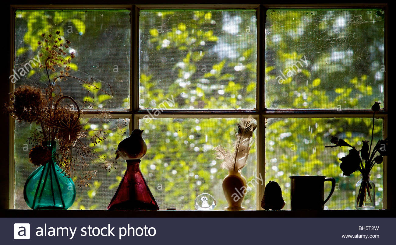 A kitchen window with warm sunlight coming through the colored glass - Stock Image