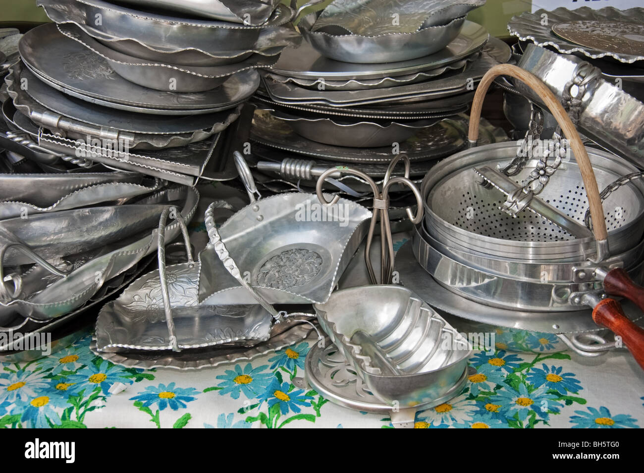 This photo shows stacks of tarnished, antique silver platters and other kitchenware. - Stock Image