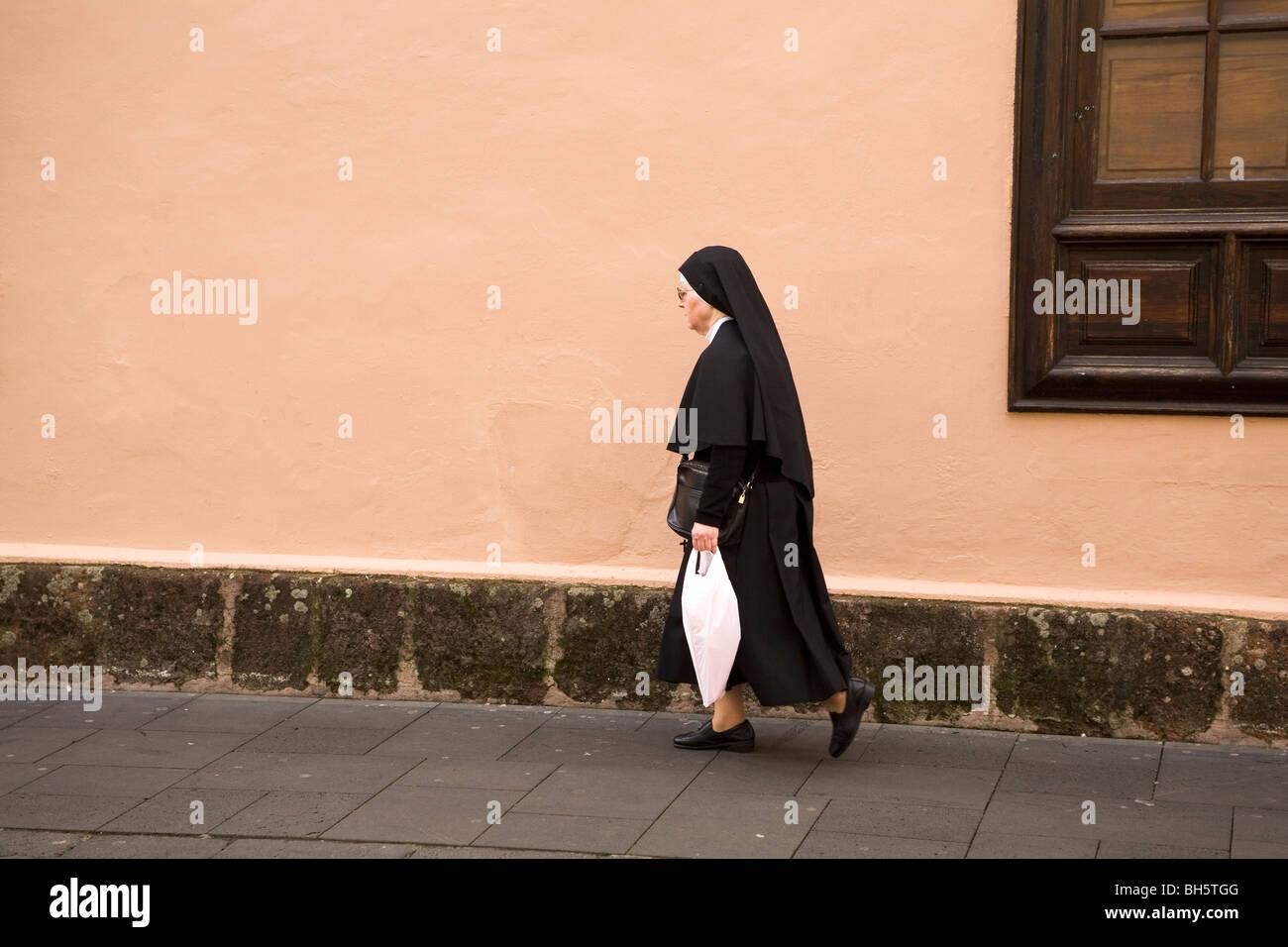 A nun walks along a street in San Cristóbal de La Laguna in Tenerife, Spain. - Stock Image