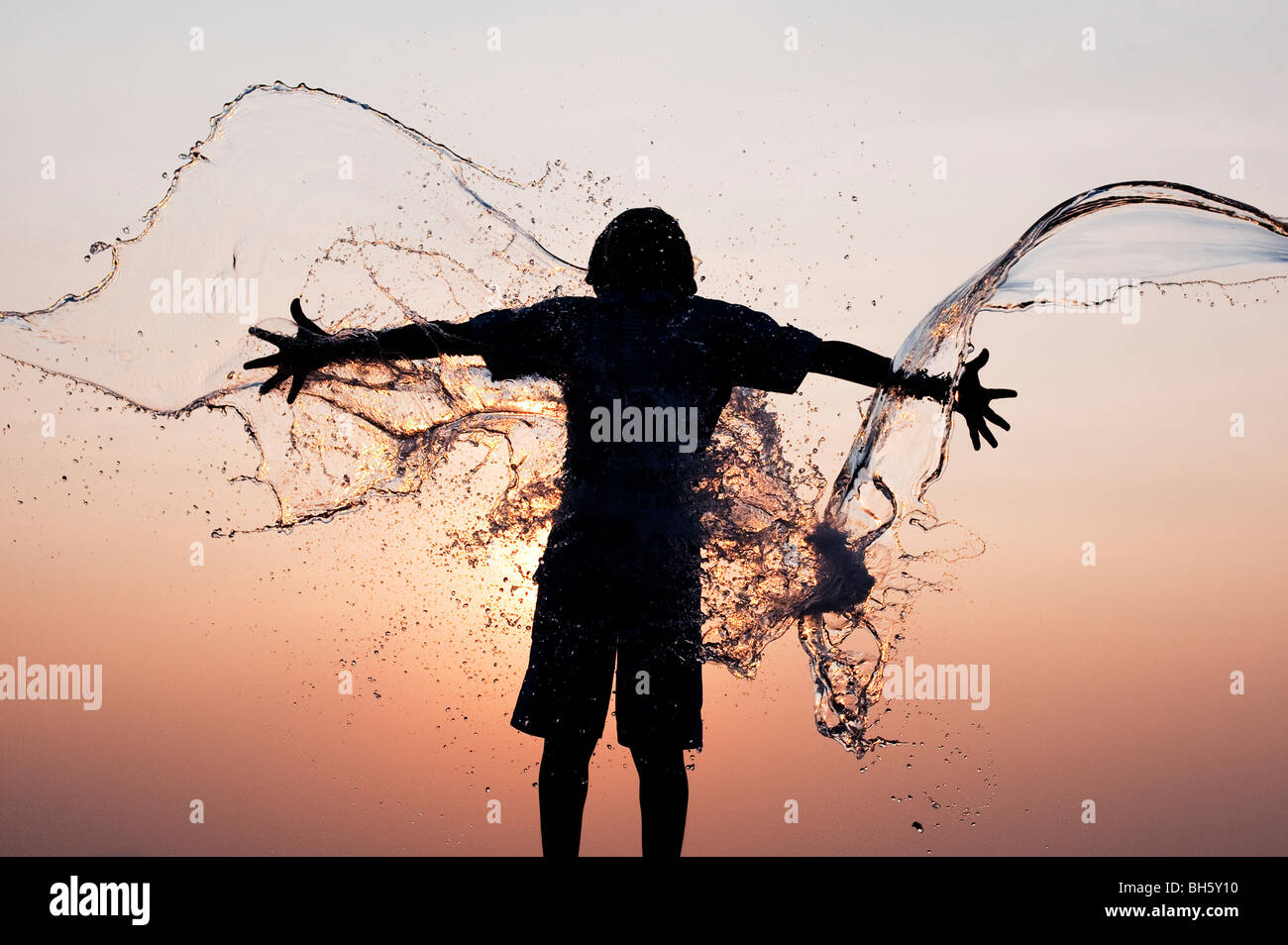 Indian boy having water thrown at him against an indian sunset. Silhouette. Andhra Pradesh, India Stock Photo