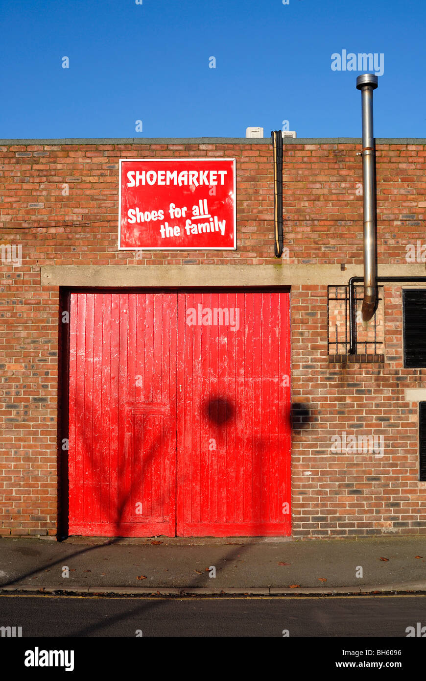 Bright red doors and red and white 'Shoemarket' sign. - Stock Image