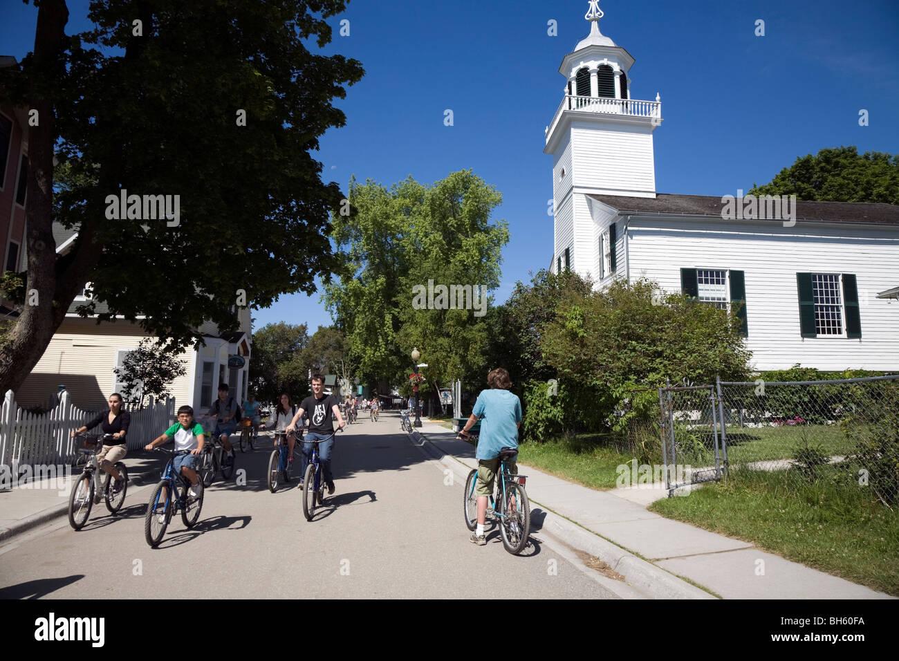 Tourists cycling past Mission Church on Mackinac Island, Michigan, USA. - Stock Image