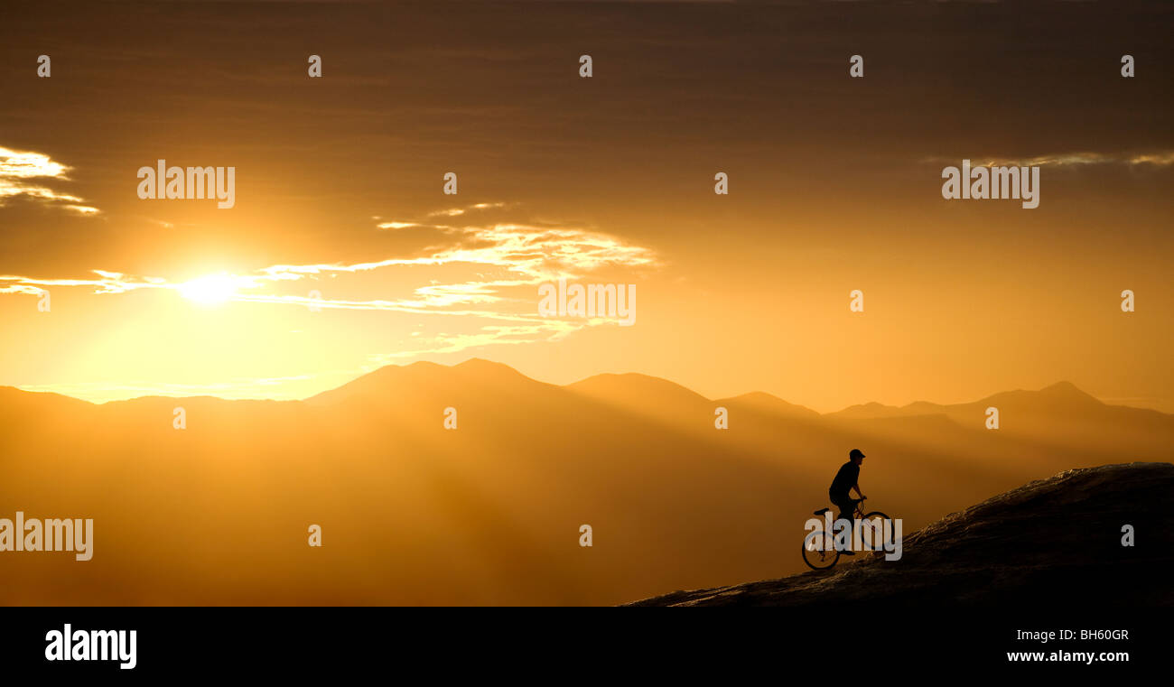 Mountain biker rides up a hill at sunset. This one is in Arizona, just west of Tucson. - Stock Image