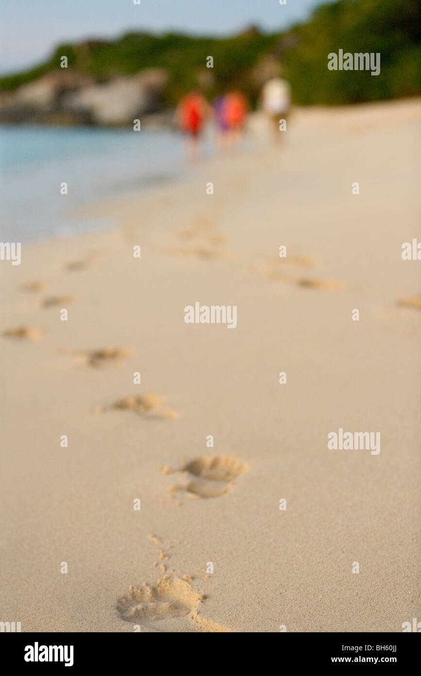 Footprints on a tropical Caribbean beach and tourists in the background. - Stock Image