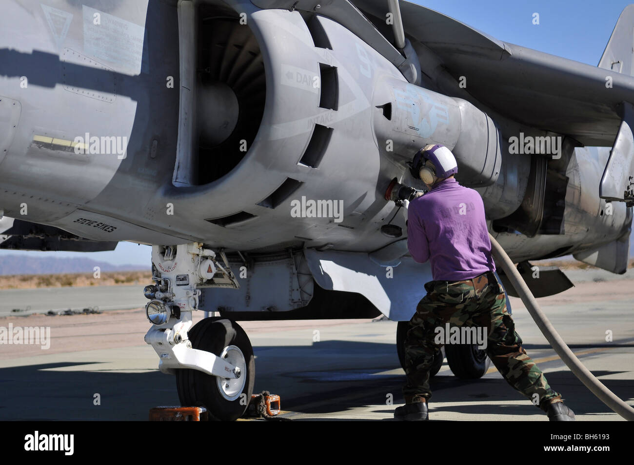 Aviation fuel technician attaches a fuel line to an AV-8B Harrier. - Stock Image