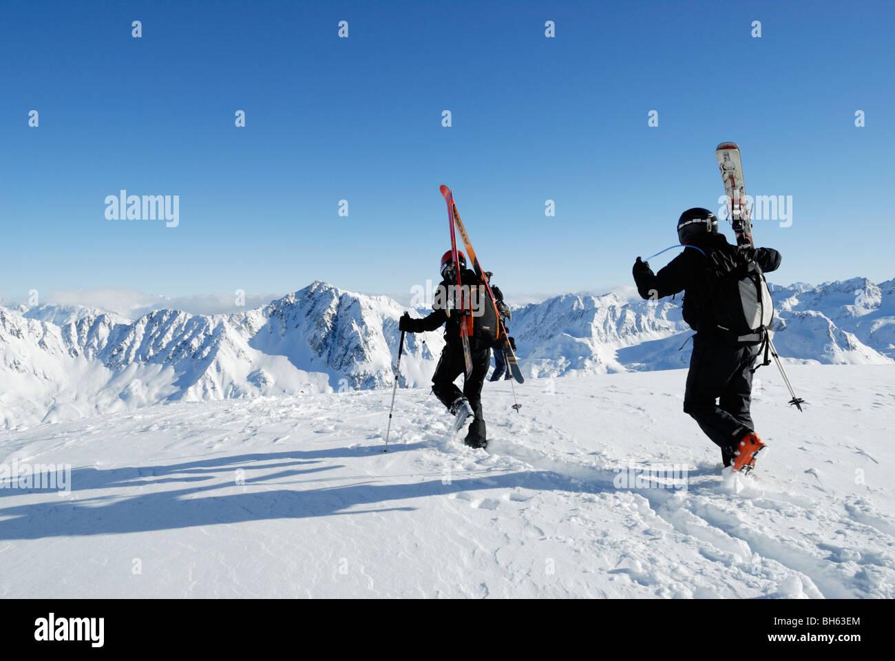 Two skiers walking and carrying their skis on off-piste terrain, Gemsstock, Andermatt, Switzerland - Stock Image