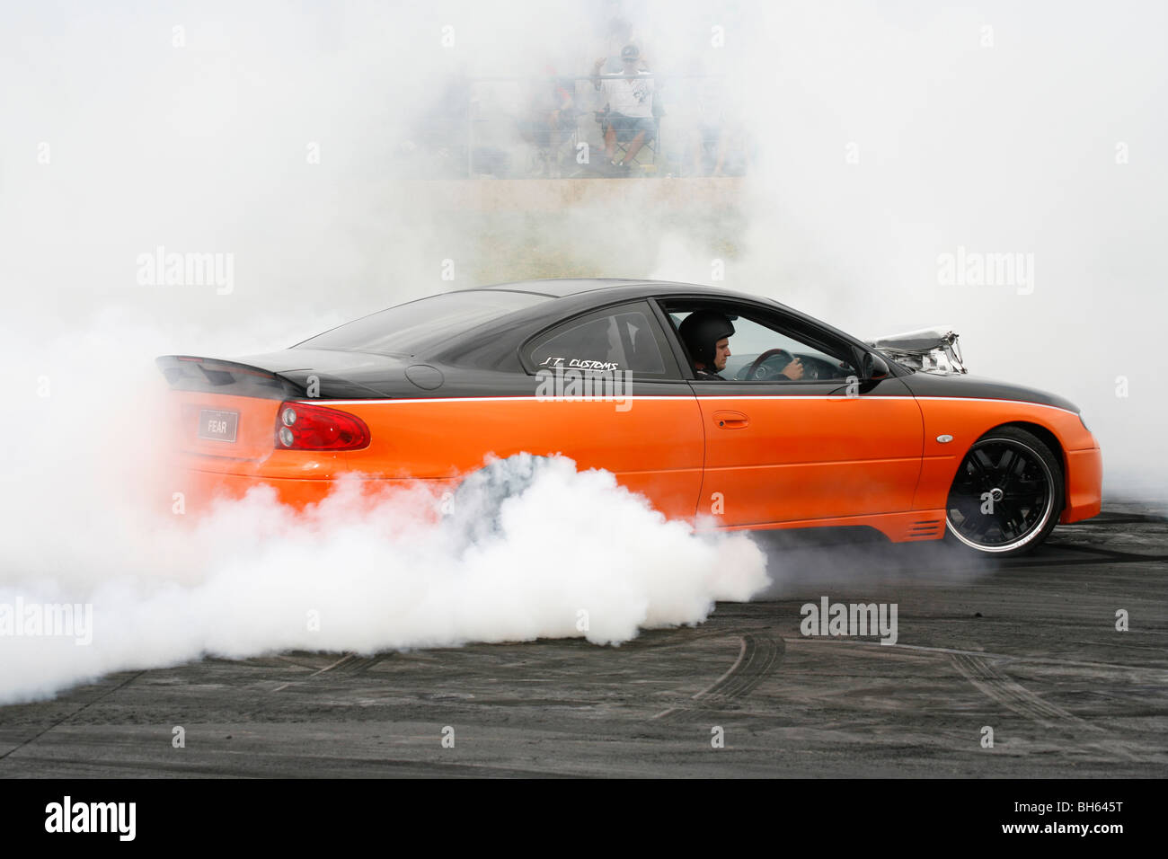 Australian burnout specialist, Fred Watson, performing a massive burnout in his Holden Monaro dubbed 'FEAR'. - Stock Image