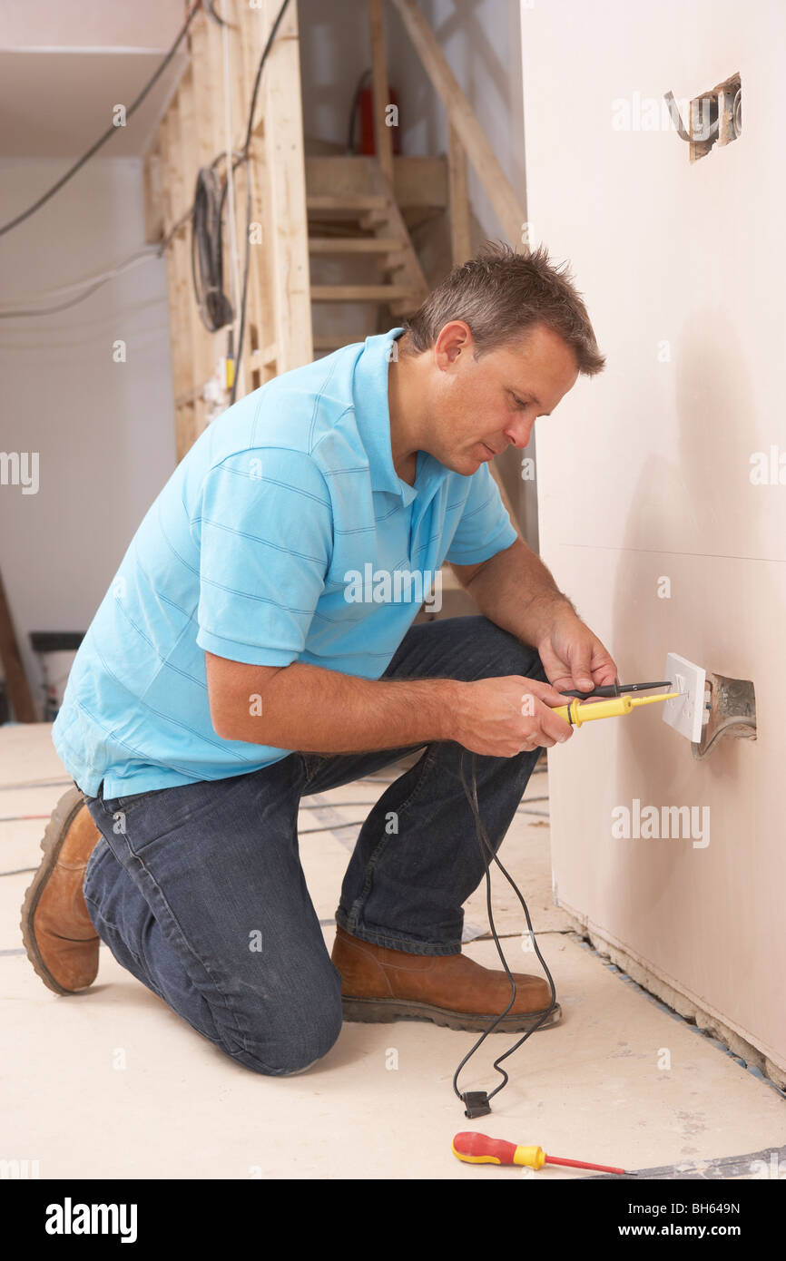 Electrician Installing Wall Socket Stock Photo