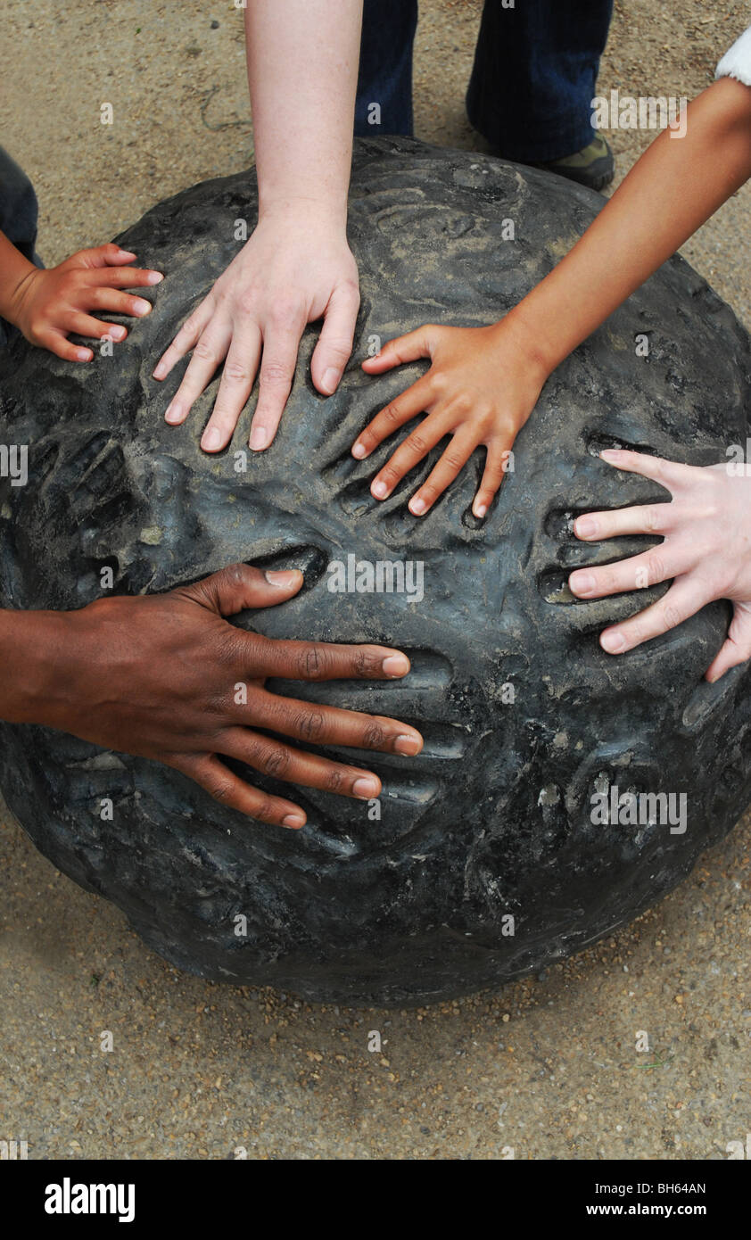 Multiple hands of different races fit into hand-prints on a piece of modern art. - Stock Image