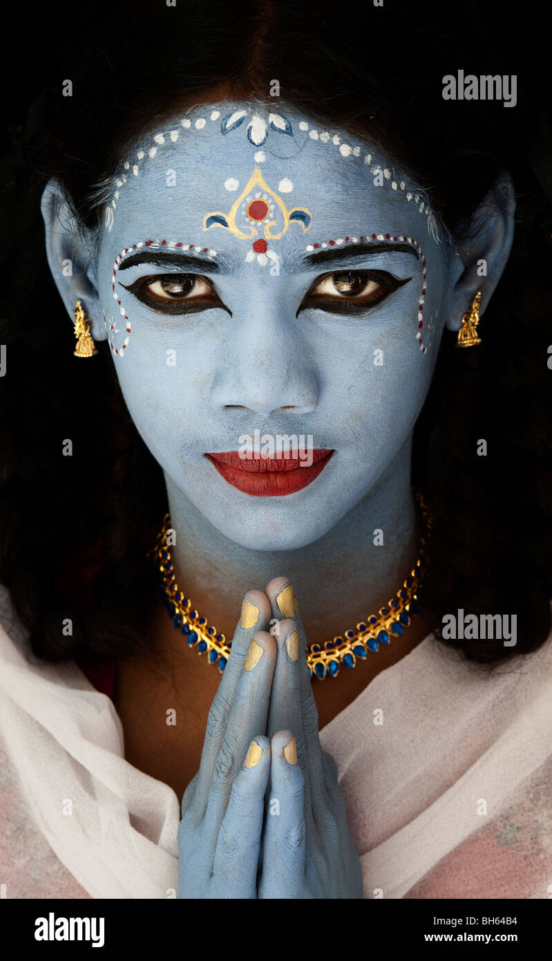 Indian girl, face painted as the Hindu goddess Sita against a black background. India - Stock Image