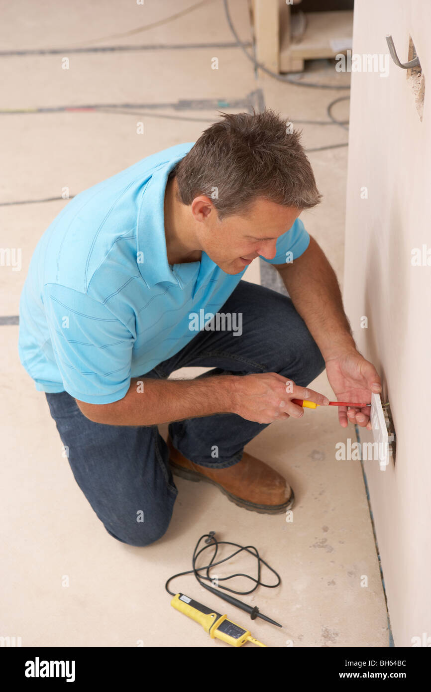 Electrician Installing Wall Socket Stock Photo