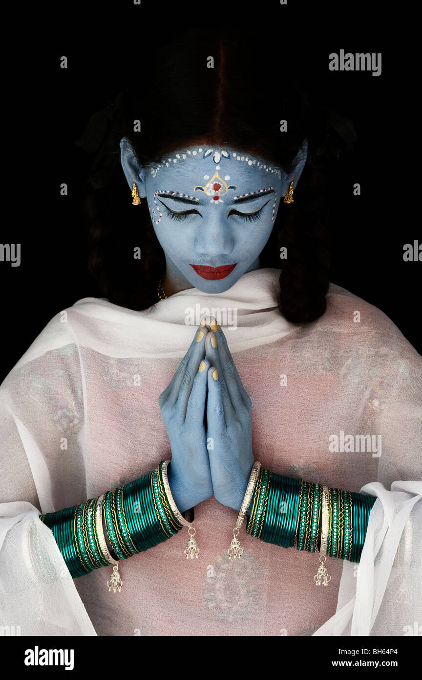 Indian girl face painted as the Hindu goddess Sita against a black background. India - Stock Image