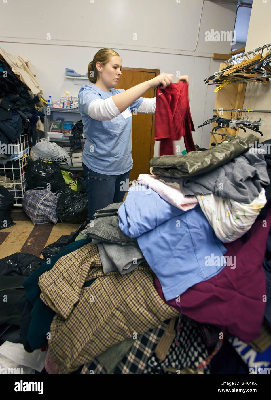 Volunteer Sorts Donated Clothing at Thrift Shop - Stock Image