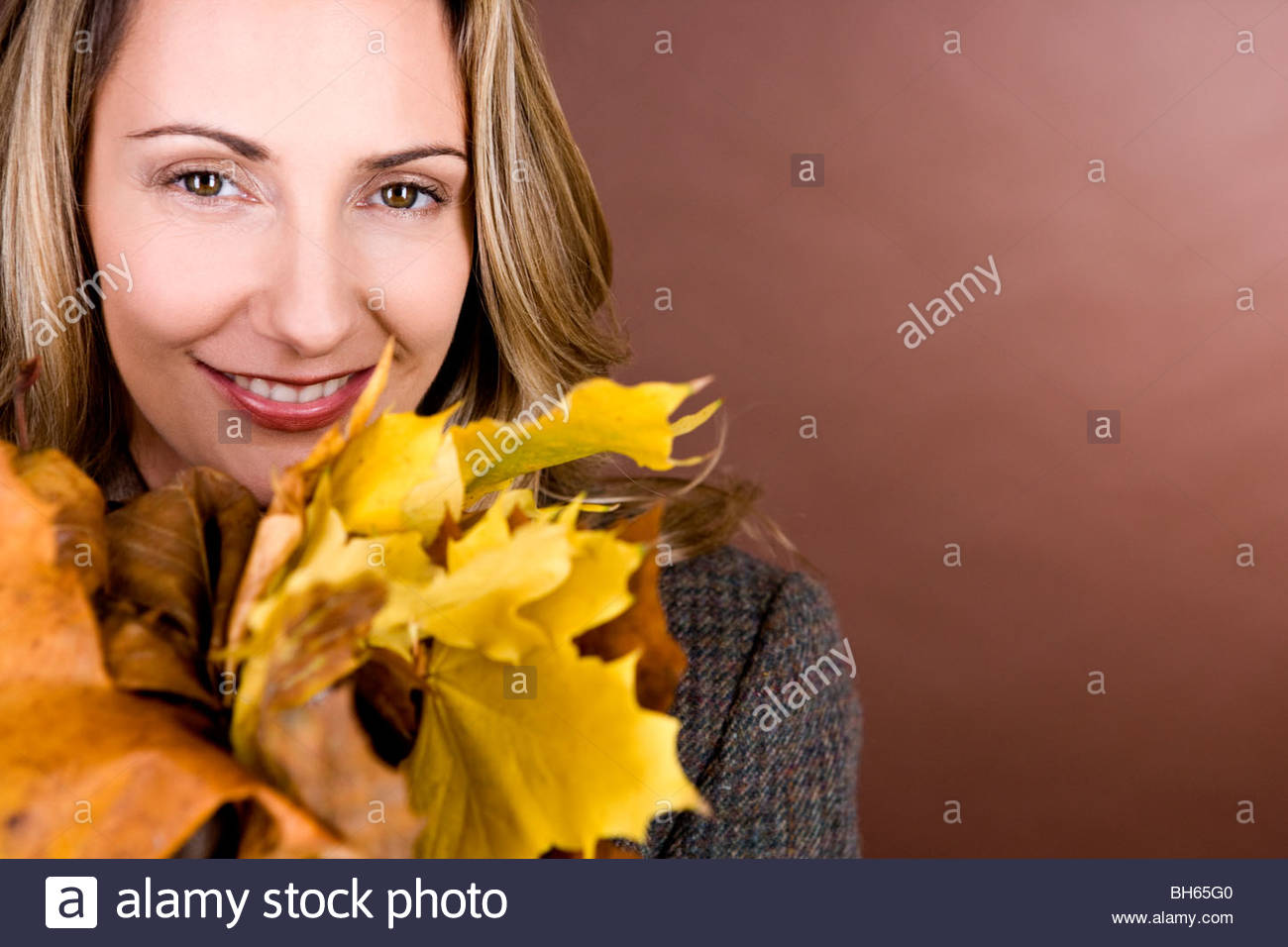 A mid adult woman holding a handful of autumn leaves - Stock Image