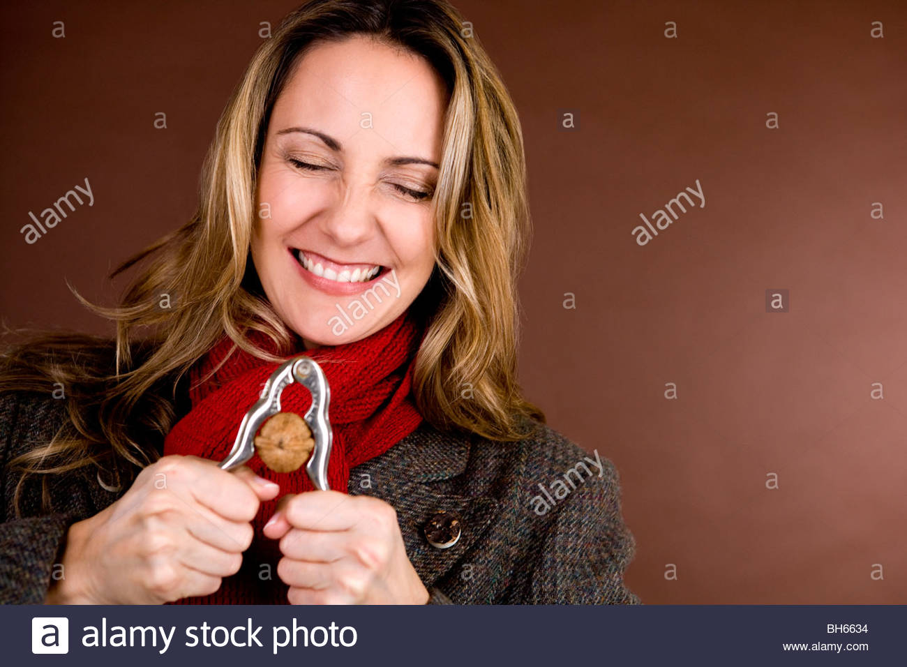 A mid adult woman cracking a nut - Stock Image