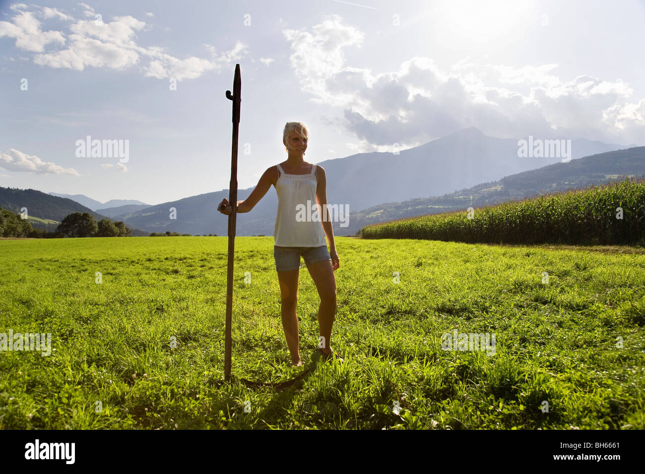 girl standing in pasture with scythe Stock Photo