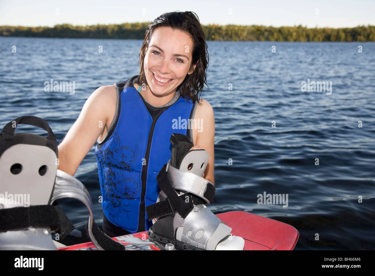 Woman standing in water with wakeboard - Stock Image