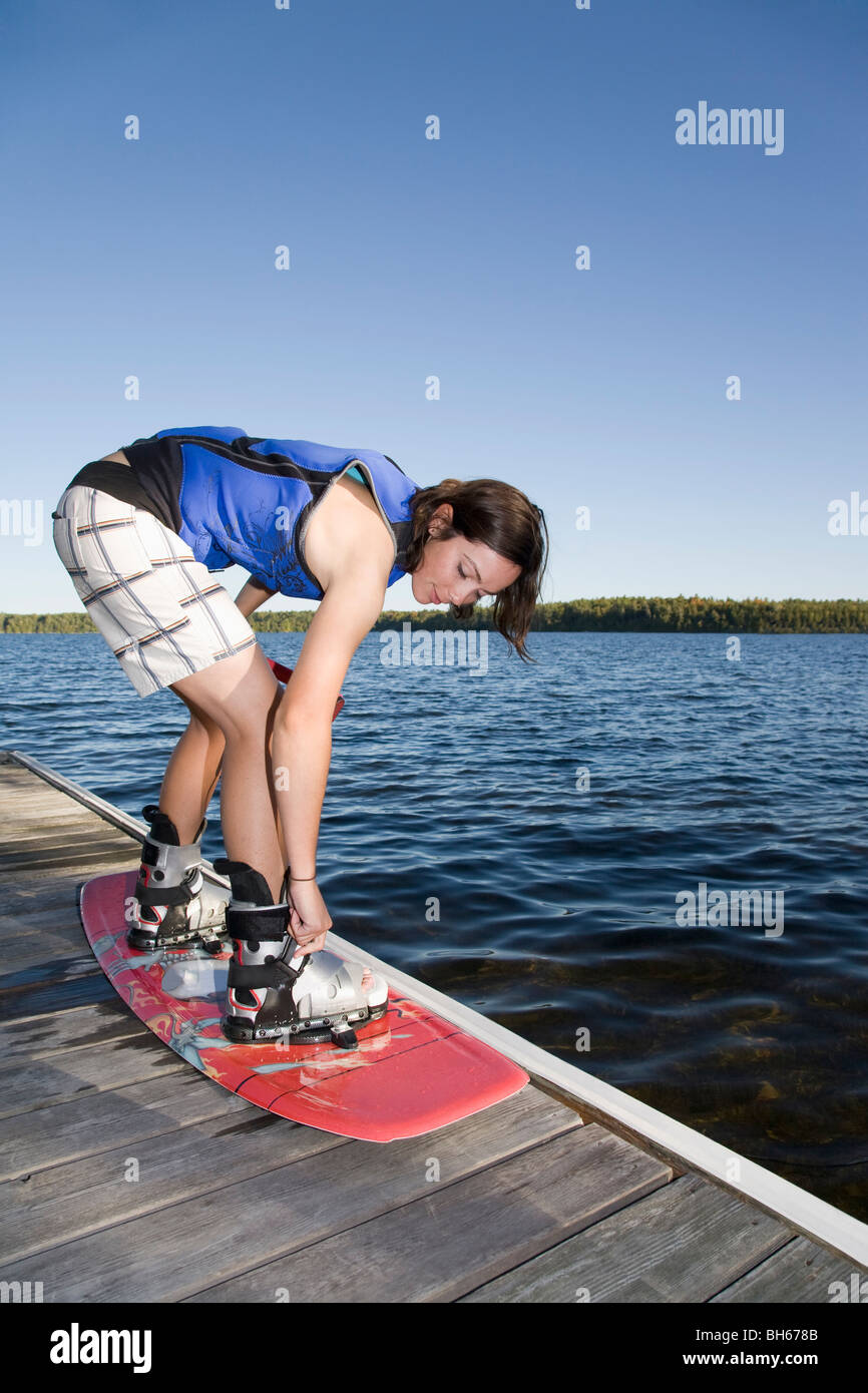 Woman strapping into wakeboard - Stock Image