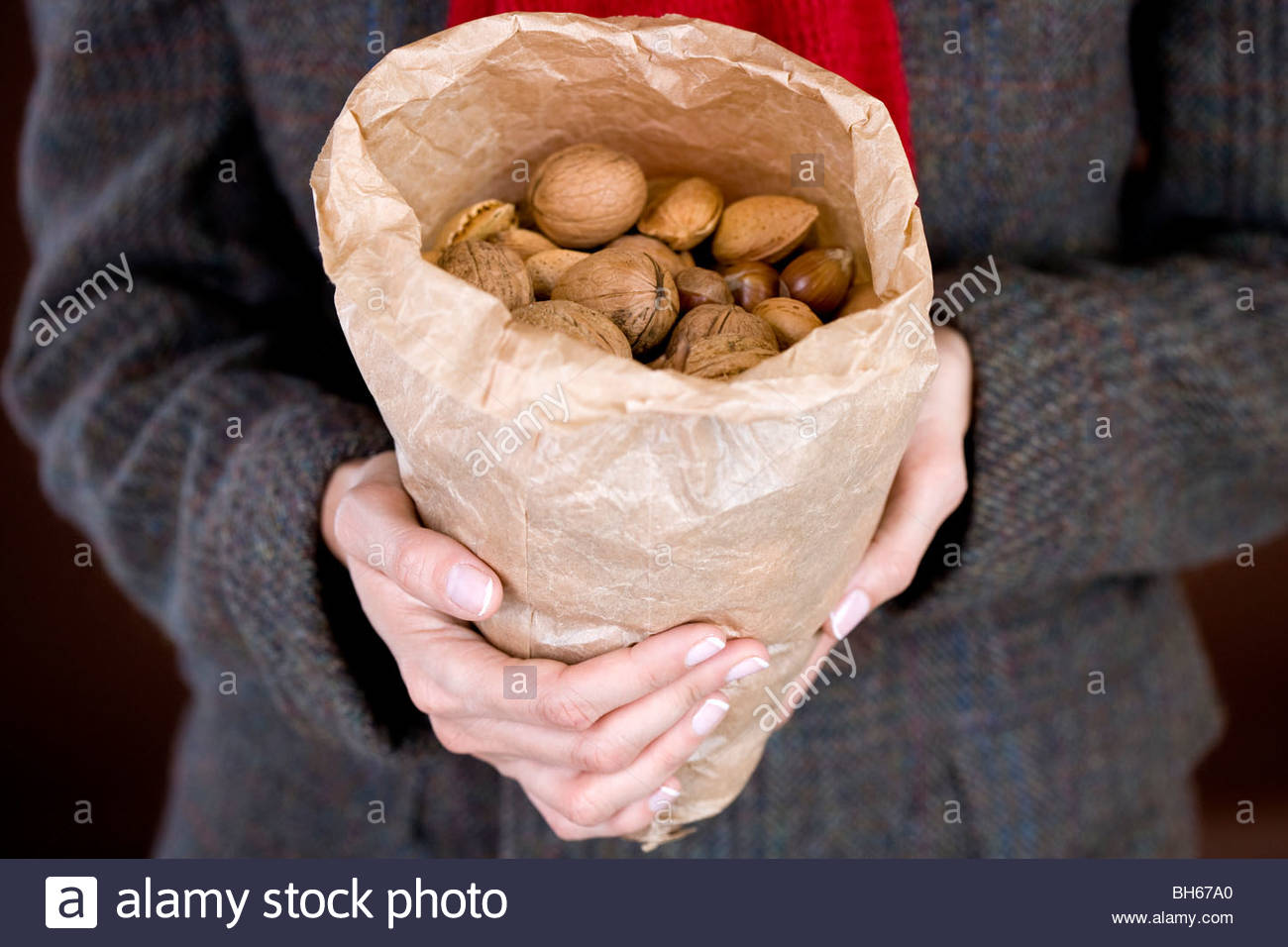 A woman holding a bag full of mixed nuts Stock Photo