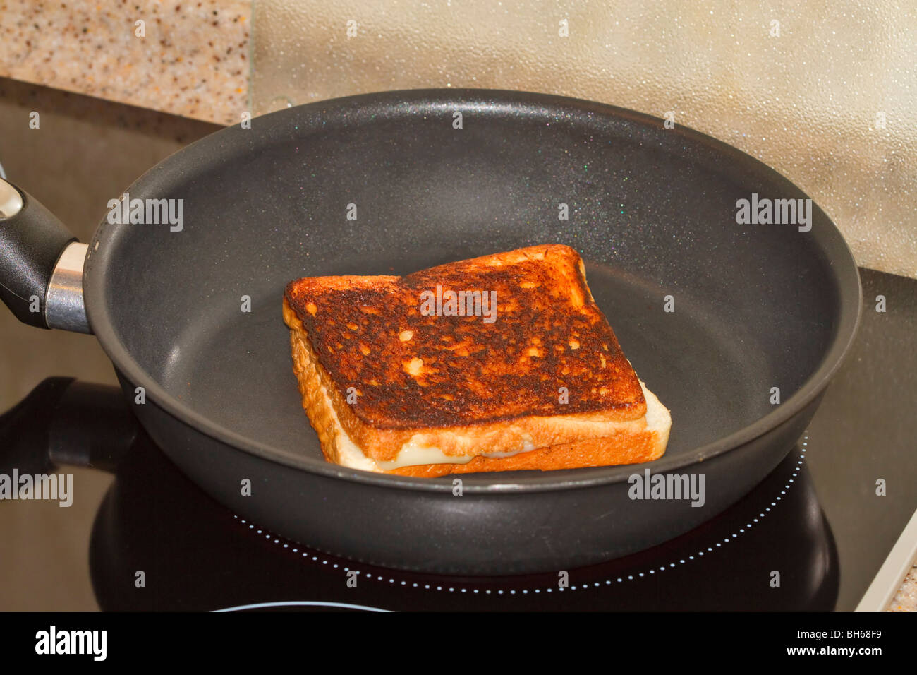 Grilled cheese sandwich in frying pan - Stock Image